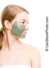 Skin care. Woman with clay mud mask on face.