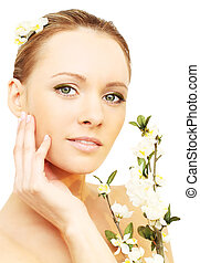 Skin care - woman with spring flowers isolated on white background