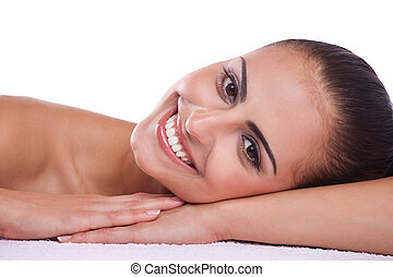 Skincare - Beautiful brunette spa woman lying on towel