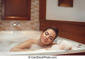 Skincare. Wellness. Beautiful Young woman relaxing in jacuzzi bath spa, Attractive girl with Clean Fresh Skin relaxing foam bath in bathroom. Beauty face care. Facial treatment brunette enjoying.