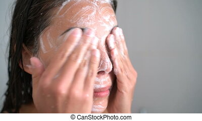 Skincare woman washing face with facewash soap in shower