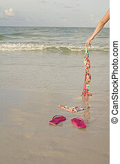 Skinny dipping concept shot showing a woman's arm dropping her top on the beach