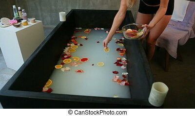 skinny girl throws citrus slices and rose petals in black...