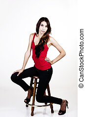 Skinny Latina Woman Sitting On Stool Red Top Blue Jeans