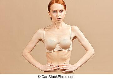 Skinny suffering female model in nude underwear tied waist with measuring tape