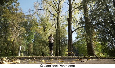 Skinny teenager girl jogging in the park while leaves fall...