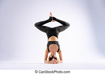 Skinny young woman standing on her head
