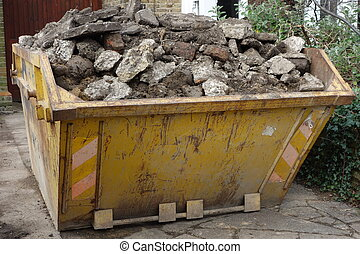 Skip - Yellow skip full to the brim with building rubble
