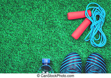 Skipping rope, water bottle and cleats against green artificial turf