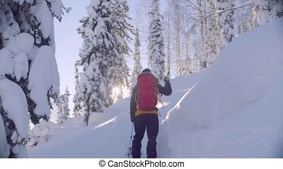 Skitour in Siberia. A man climbing up the hill in a snowy...