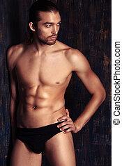 skivvies ad - Sexual muscular nude man posing over dark...