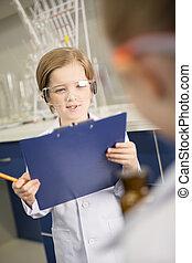 skolpojke, in, skyddande skyddsglasögon, intagande antecknar, in, kemisk, laboratorium