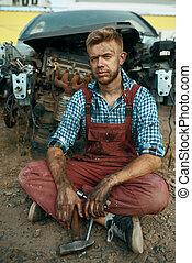 skrotupplag, manlig, repairman, sittande, jord, bil