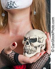Skull in the hand of girl in mask. Helloween
