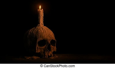 Skull With Melted Candle Burning In The Dark