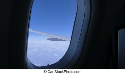 Sky and earth through the porthole of a flying airplane,...