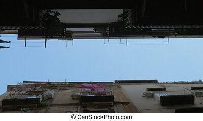 Bottom view of the aged buildings and sky. Linen hanging on the balconies and waving in the wind. Naples, Italy