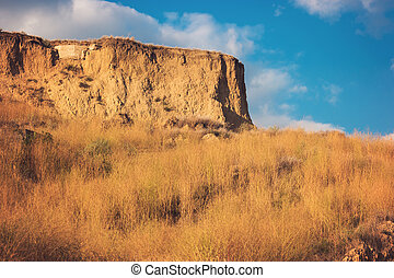 Sky and sandy cliff.