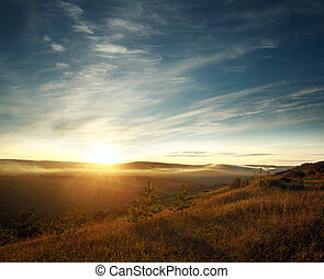 Sky in rays of setting sun over the hills and fields