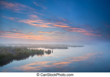 sky reflected in lake at misty morning