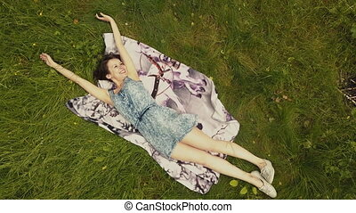 Sky view beautiful young woman lying on grass in summer day
