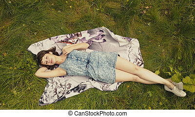 Sky view cheerful young woman on green grass. Beautiful girl relaxing on grass