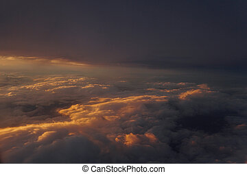 Sky with clouds at sunset from inside the plane landscape