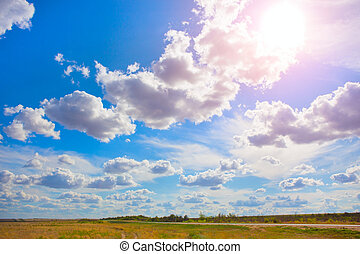 sky with clouds over field and road