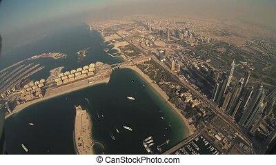 Skydiver fly above coast in Dubai. Parachute. Cityscape. Extreme flight. Ocean