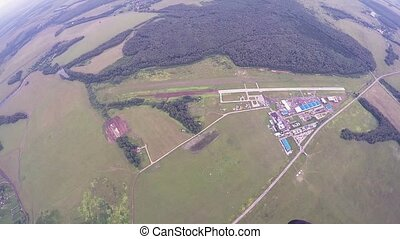 Skydiver fly on parachute above green fields. High altitude. Summer day. Extreme