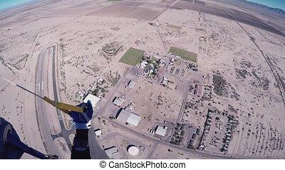 Skydiver girl parachuting above Arizona. Flight. Sunny day....