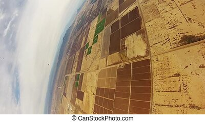 Skydiver parachuting above sands of Arizona. Extreme sport....