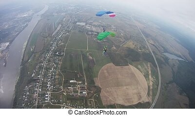 Skydivers fly in sky over green field. Colorful parachutes....