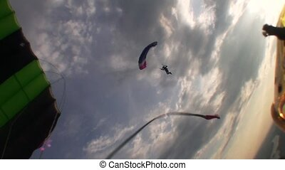 Skydivers parachuting in evening sky. Clouds. Speed. Sunset....
