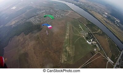 Skydivers with colorful parachutes balance in sky over green field. River.