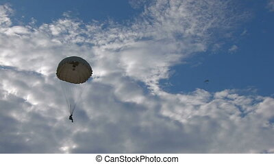 skydiving in blue sky with clouds
