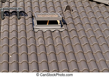 Skylight - Photo of the roof window on a grey tiled rooftop