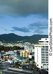 skyline cityscape view of downtown port of spain trinidad showing national performing arts center offices and the queen\'s park savannah and woodford park with mountains in background
