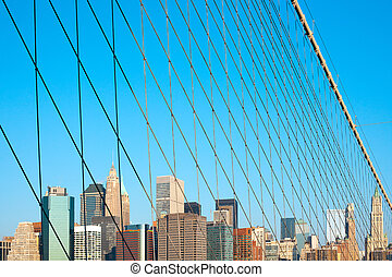 Skyline of buildings at Wall Street and Downtown Manhattan behind the cables of Brooklyn Bridge, Manhattan, New York City, NY, USA