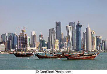 Skyline of Doha with traditional arabic dhows. Qatar, Middle...