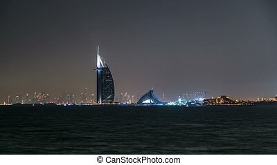 Skyline of Dubai at night timelapse with Burj al Arab in foreground in Dubai, United Arab Emirates
