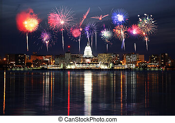 Madison Wisconsin skyline has the reflections of the cities lights in Lake Menona with a fireworks celebration overhead