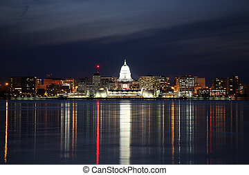 the Madison Wisconsin skyline during early evening has the reflections of the cities lights in Lake Menona