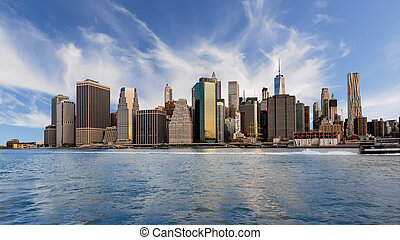 Skyline of New York with clouds in the sky and reflect in the water