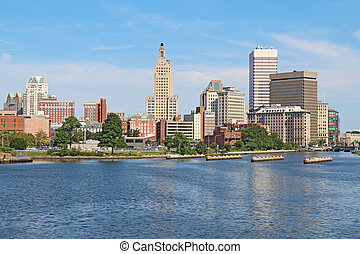 View of the skyline of Providence, Rhode Island, from the far side of the Providence River against a blue sky and white clouds