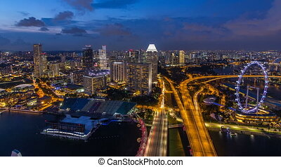 Skyline of Singapore with famous Singapore Ferries Wheel day to night timelapse at twilight