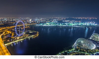 Skyline of Singapore with famous Singapore Ferries Wheel night timelapse
