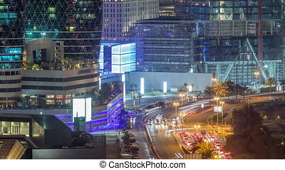 Skyline view of intersection traffic on Al Saada street near DIFC night timelapse in Dubai, UAE. Illuminated skyscrapers in financial centre aerial view from above in downtown