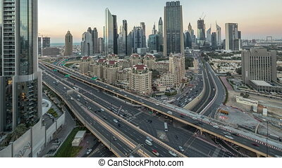 Skyline view of intersection traffic near Sheikh Zayed Road and DIFC day to night transition timelapse in Dubai, UAE. Illuminated skyscrapers in financial centre aerial view from above in downtown