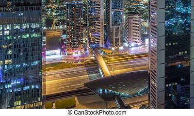 Skyline view of the buildings of Sheikh Zayed Road and DIFC night timelapse in Dubai, UAE. Illuminated skyscrapers in financial centre aerial view from above with metro station